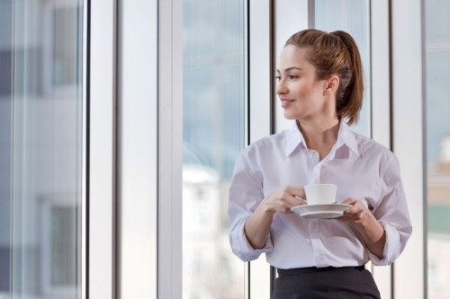 Pretty woman enjoying coffee break at her workplace