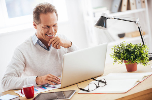 Satisfied with his work. Cheerful mature man working on laptop and smiling while sitting at his working place